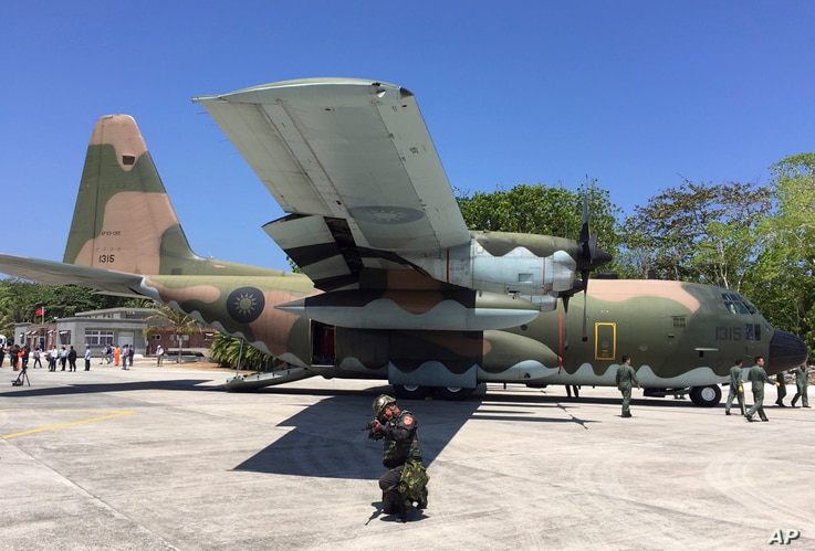 Taiwan coast guard secure a C-130 military transport plane on the tarmac of Taiping island, also known as Itu Aba, in the Spratly archipelago, roughly 1600 kms. (1000 miles) south of Taiwan, March 23, 2016.