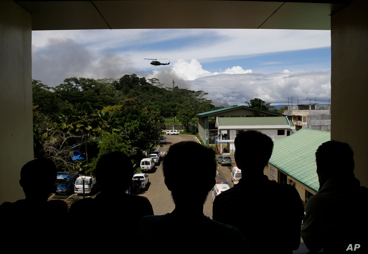 Nasir Abdul (second from right) and other evacuees watch as a military helicopter passes by black smoke from burning houses outside a temporary evacuation center at the provincial government capitol in Marawi city, southern Philippines, June 9, 2017....