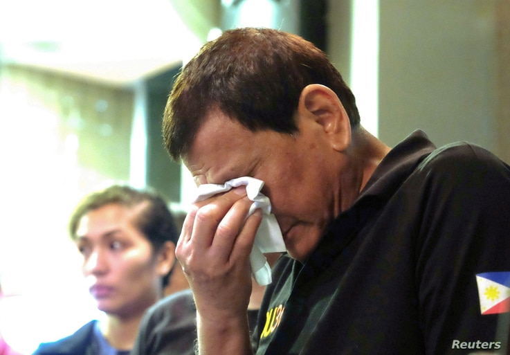 President Rodrigo Duterte weeps as he comforts family members of fire victims in Davao city in Philippines, Dec. 24, 2017.