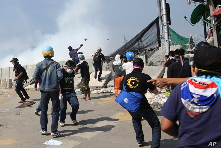 Anti-government protesters throw rocks after riot police fired tear gas at them near the Government House in Bangkok, Dec. 2, 2013.