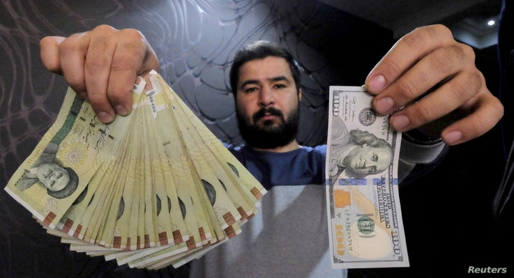A money changer poses with a U.S dollar (R) and the equivalent in Iranian rials (L) in Tehran's business district, Iran, January 20, 2016.  REUTERS/Raheb Homavandi/TIMA