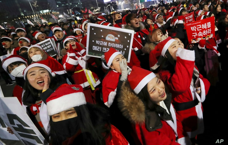 People wearing Santa Claus costumes shout during a rally calling for South Korean President Park Geun-hye to step down in Seoul, South Korea, Dec. 24, 2016.