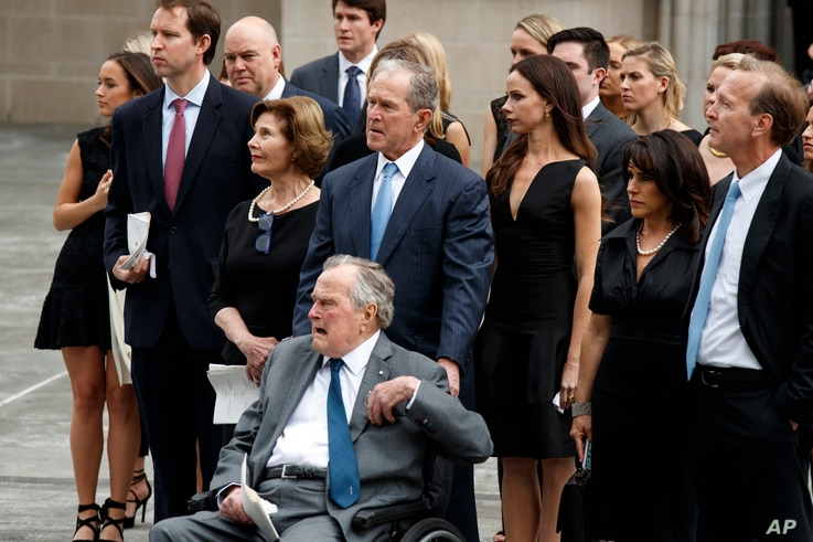 Former President George W. Bush and his father former President George H.W. Bush watch as the casket of former first lady Barbara Bush is loaded into a hearse at St. Martin's Episcopal church, April 21, 2018, in Houston