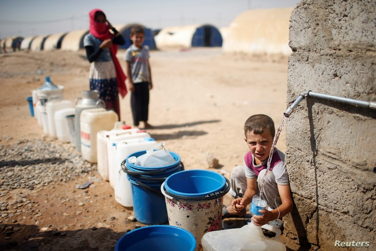 A displaced Iraqi boy fills a bottle with water in Jada camp south of Mosul, Iraq Aug. 9, 2017.