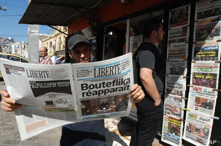 FILE - The local newspaper Liberte is among the publications seen at a newstand in Algiers, Algeria, June 13, 2013.