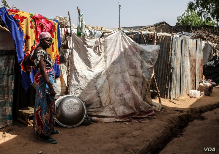A woman stands outside a makeshift house at the EYN CAN Center internally displaced persons camp in Maiduguri, Nigeria on March 24, 2016.