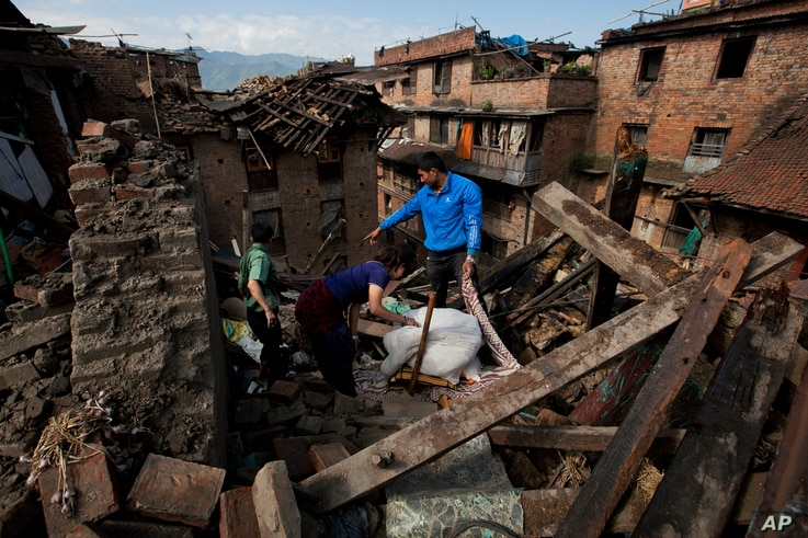 FILE - In this April 27, 2015 file photo a Nepalese family collects belongings from their home destroyed in Saturday's earthquake, in Bhaktapur on the outskirts of Kathmandu, Nepal. Last year saw the lowest financial costs from natural disasters worl...