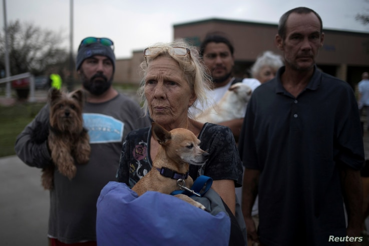 FILE PHOTO: Julie holds her dog Pee-wee as they stand in line to be evacuated to Austin after losing their home to Hurricane Harvey in Rockport, Texas, Aug. 26, 2017.