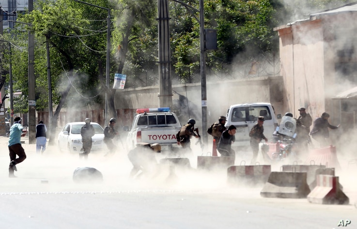 Security forces run from the site of a suicide attack after the second bombing in Kabul, Afghanistan, Monday, April 30, 2018.
