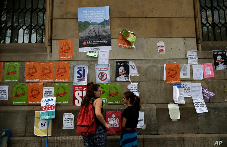 People stand in front of banners displayed on the wall regarding the independence referendum, outside the public university in Barcelona, Spain, Sept. 26, 2017.