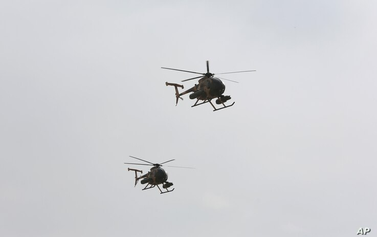 FILE - U.S.-made MD-530 Helicopters fly over the Hamid Karzai International Airport during a display of newly-delivered assets by the Afghan Air Force in Kabul, Afghanistan, Feb. 11, 2016.