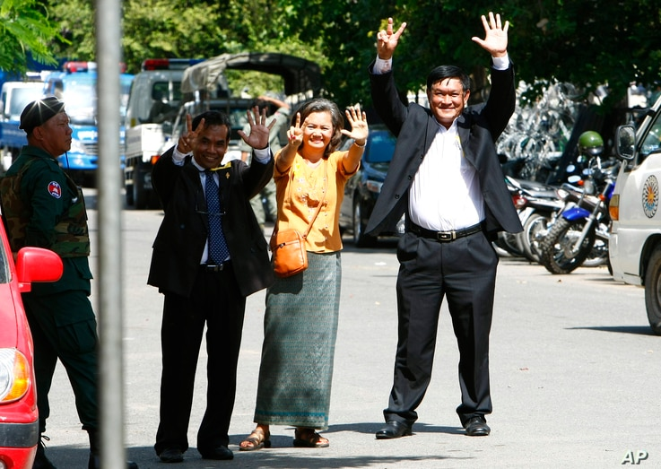 Cambodian lawmakers from the main opposition party of Cambodia National Rescue Party (CNRP), from right, Men Sothavrin, Mu Sochua and Keo Phirum gesture to make the number seven, the party's ballot number, as they are detained by authorities at Freed...