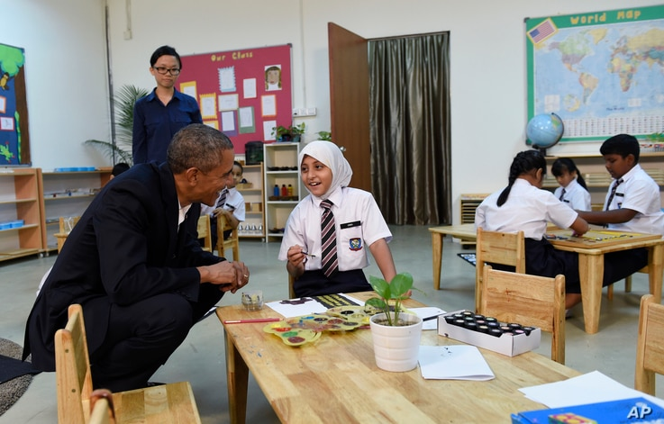 President Barack Obama listens to a girl while meeting with children during his tour to the Dignity for Children Foundation in Kuala Lumpur, Malaysia, Nov. 21, 2015.