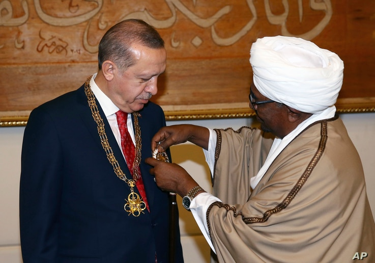 FILE - Sudan's President Omar al-Bashir, right, presents Turkey's President Recep Tayyip Erdogan with his country's highest medal during a ceremony in Khartoum, Sudan, Sunday, Dec. 24, 2017.  Erdogan is in Sudan for a two-day State visit.