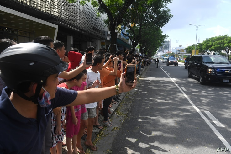 Vietnamese line the street as the motorcade transporting U.S. President Donald Trump passes by, after his arrival for the Asia-Pacific Economic Cooperation (APEC) Summit in Danang, Vietnam, Nov. 10, 2017.