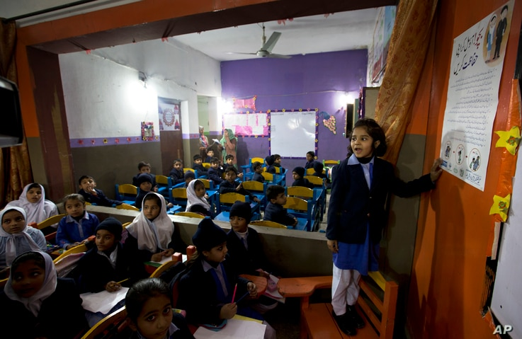 A Pakistani student shares information with her classmates regarding awareness about rape and kidnap attempts at a school in Kasur, Jan. 19, 2018.