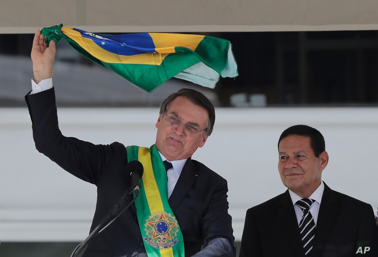 Brazil's President Jair Bolsonaro, flanked by his Vice President Hamilton Mourao, waves the national flag from the Planalto Presidential palace, in Brasilia, Brazil, Jan. 1, 2019.