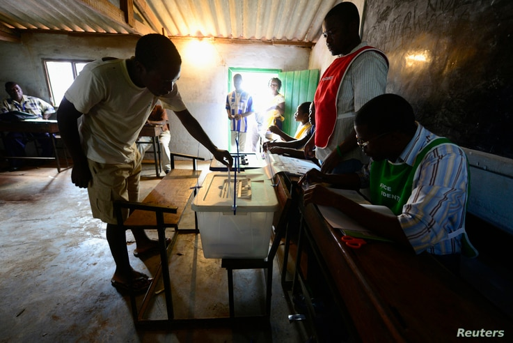 A man casts his ballot at a voting station near Gorongosa in central Mozambique, Nov. 20, 2013.