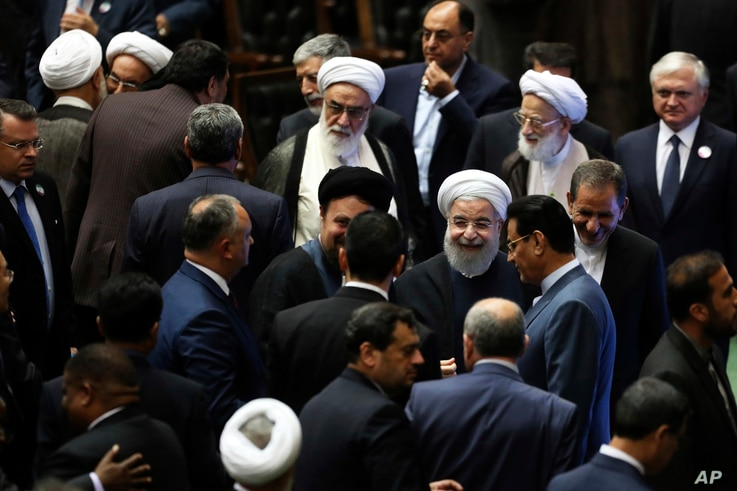 Iran's President Hasan Rouhani, center, leaves the parliament at the end of his swearing-in ceremony for the second term in office, in Tehran, Iran, Saturday, Aug. 5, 2017.
