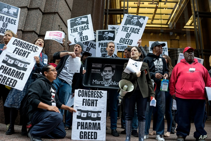 FILE -  activists hold signs containing the image of Turing Pharmaceuticals CEO Martin Shkreli in front the building that houses Turing's offices, during a protest in New York highlighting pharmaceutical drug pricing, October 1, 2015.