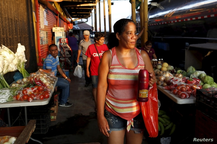 Cuban migrant Yunia Alvarez, a nurse who ran out of money, works selling coffee on the street in Paso Canoas, Panama, on the border with Costa Rica, March 22, 2016. Alvarez says she has the funds her family needs to reach the U.S.; money she makes se...