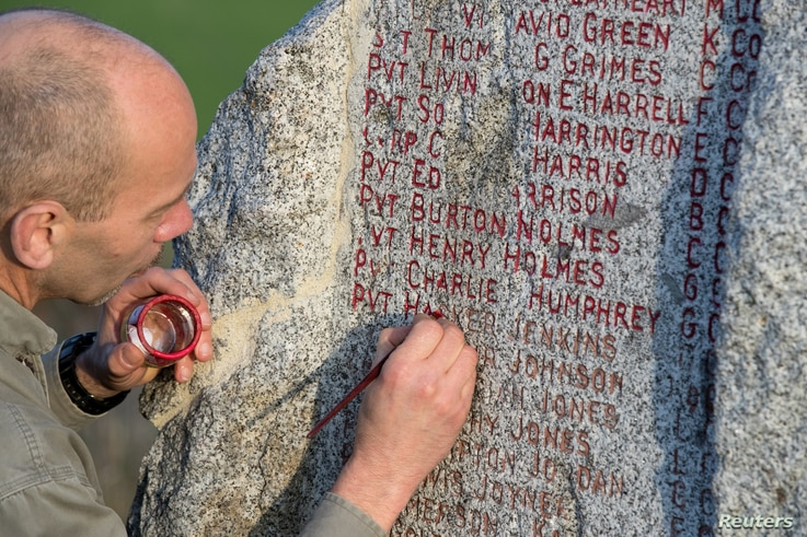 Local man Frank Lesjean repaints the names of fallen U.S. soldiers of the First World War's 371st infantry regiment, an African American unit, onto a granite monument on a ridge surrounded by fields, near the eastern French village of Ardeuil-et-Mo...