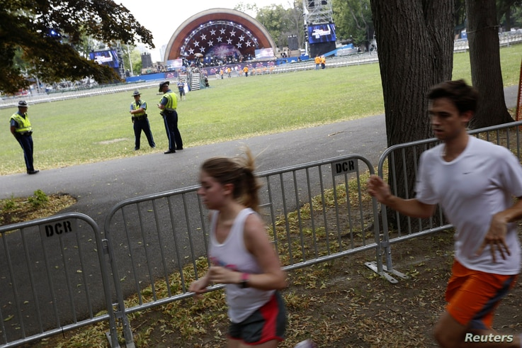 Runners pass by the Hatch Memorial Shell stage as officials prepare to celebrate Independence Day a day early in Boston, Massachusetts, July 3, 2014.