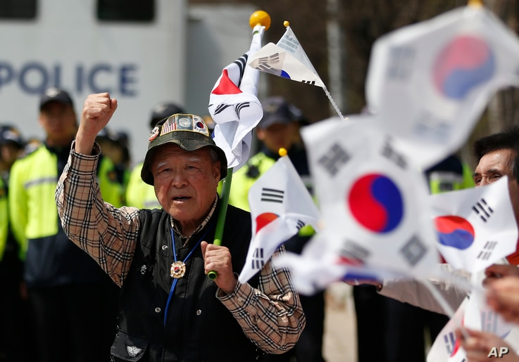 South Korean conservatives activist shout slogans with national flags as police block the conservative activists attempting to release balloons with leaflets during a rally at the border city with North Korea, in Paju, South Korea, April 15, 2016.