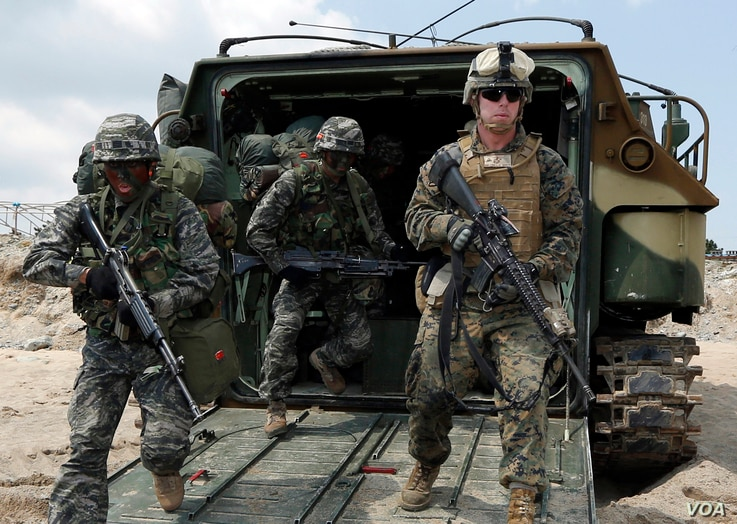 FILE - U.S. and South Korean Marines run from a South Korean assault amphibious vehicle during joint military exercises in Pohang, south of Seoul, April 26, 2013.