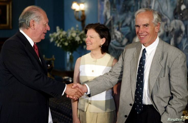 FILE - U.S. millionaire Douglas Tompkins (R), accompanied by his wife (C) shakes hands with Chilean President Ricardo Lagos (L) after signing an agreement at La Moneda Presidential Palace, in Santiago, Dec. 9, 2003.