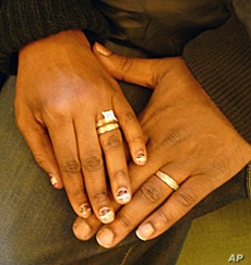 Hasson and Nicole show off their wedding rings.