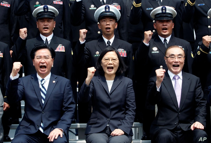 FILE - Taiwan's President Tsai Ing-wen, center, along with Defense Minister Feng Shih-kuan, right, and Secretary-General of National Security Council Joseph Wu, left, cheer with navy officers during a visit to Zuoying Naval base in Kaohsiung, souther...