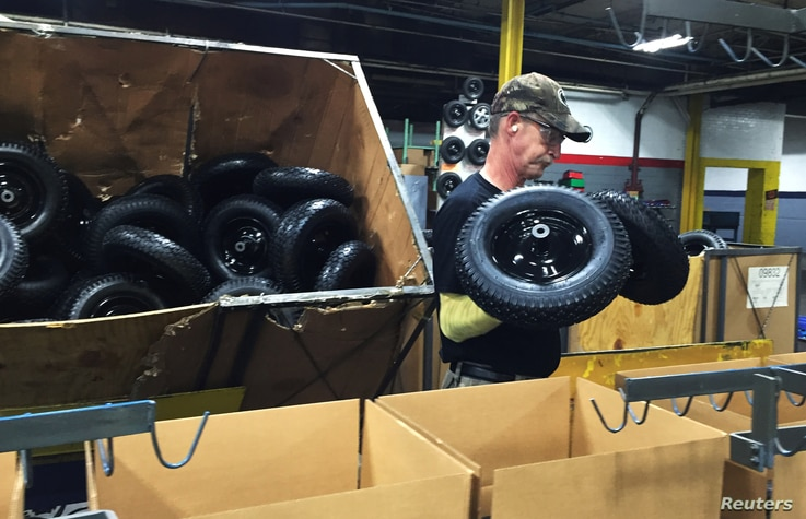 Randy Blantz, 57, unloads Chinese-made wheels near the end of the assembly line at the AMES Companies wheelbarrow factory, the largest wheelbarrow factory in the world, in Harrisburg, Pennsylvania, June 29, 2017.