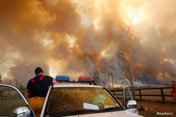 FILE - A fireman climbs down from his truck as a bushfire approaches the town of Labertouche, 90 km (56 miles) east of Melbourne, Feb. 7, 2009.