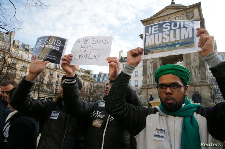 "French Muslim youths hold placards which read, ""I am Muslim. I love my Prophet"" (R) and ""I am Muhammad. I belong to the Muslim community and I am anti-terrorist"" during a demonstration in central Paris January 18, 2015. Up to two hundred French Musli..."