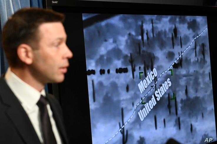 With surveillance footage in the background, U.S. Customs and Border Patrol Commissioner Kevin McAleenan speaks during a news conference in Washington, March 5, 2019.