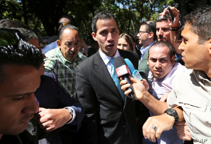 FILE - Opposition National Assembly President Juan Guaido talks with reporters upon his arrival to the Venezuelan Central University for a conference on economic plans for reviving the country in Caracas, Venezuela, Jan. 31, 2019.
