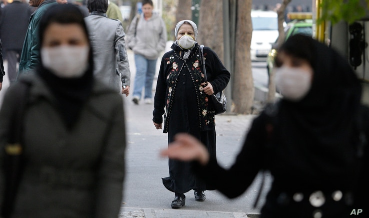 FILE - Iranian women wear masks to help guard against dangerous levels of air pollution as they walks in the center of the smog-filled capital, Tehran, Iran.