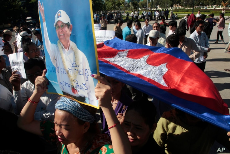 A supporter of the opposition Cambodia National Rescue Party holds a portrait of the party leader Kem Sokha during a rally in Phnom Penh, Cambodia, Sept. 26, 2017. The court rejected a request for his release on bail. Kem Sokha has been charged with ...