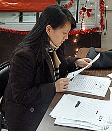 Substitute Santa Erica sifts through letters before deciding which child she will buy for.