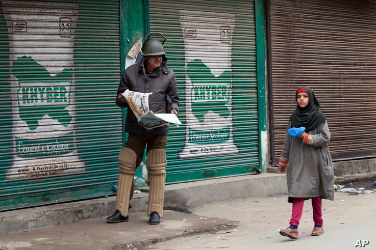 An Indian policeman reading newspaper watches a Kashmiri girl walk past him during restrictions in Srinagar, Indian controlled Kashmir, Friday, Nov. 6, 2015.