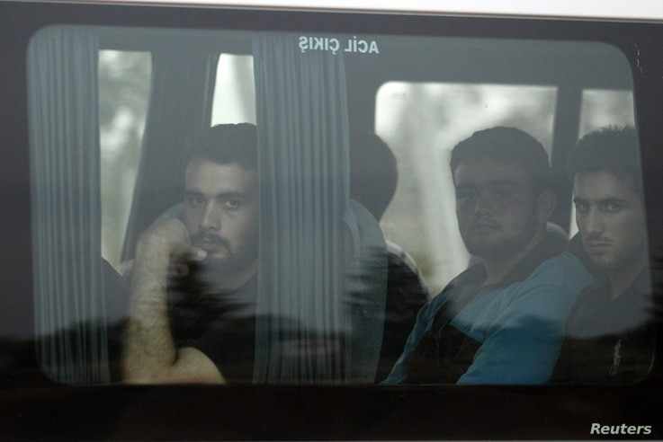 New Syrian refugees look out from their bus as they arrive at a refugee camp in the Turkish border town of Reyhanli in Hatay province July 29, 2012.