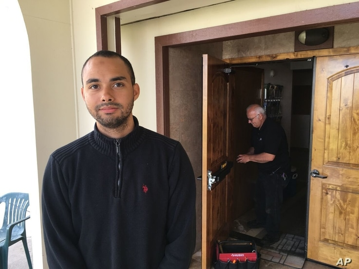 Drew Williams, a member of the Eugene Islamic Center, poses for a portrait outside the building in Eugene, Oregon, as locksmith Jim King upgrades the locks on the front doors, June 1, 2017..