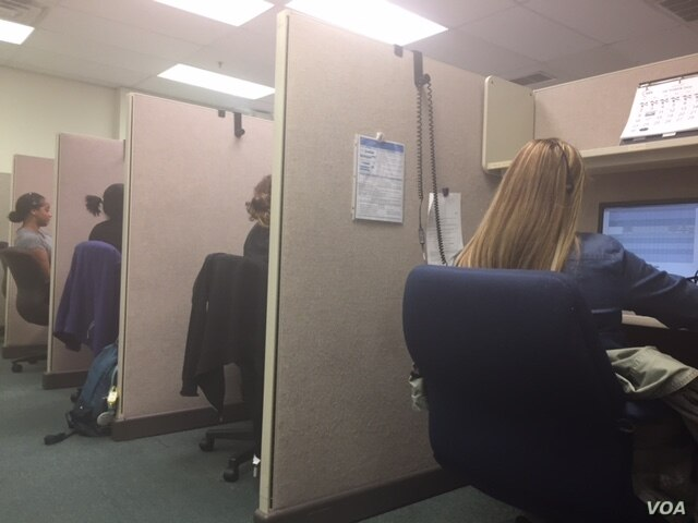 """A bank of phone interviewers conducting surveys at SSRS. Valentina Martinez (in foreground) says her constant battle is to convince respondents that she's not a telemarketer. """"We're not selling you anything."""" (C. Presutti/VOA)"""