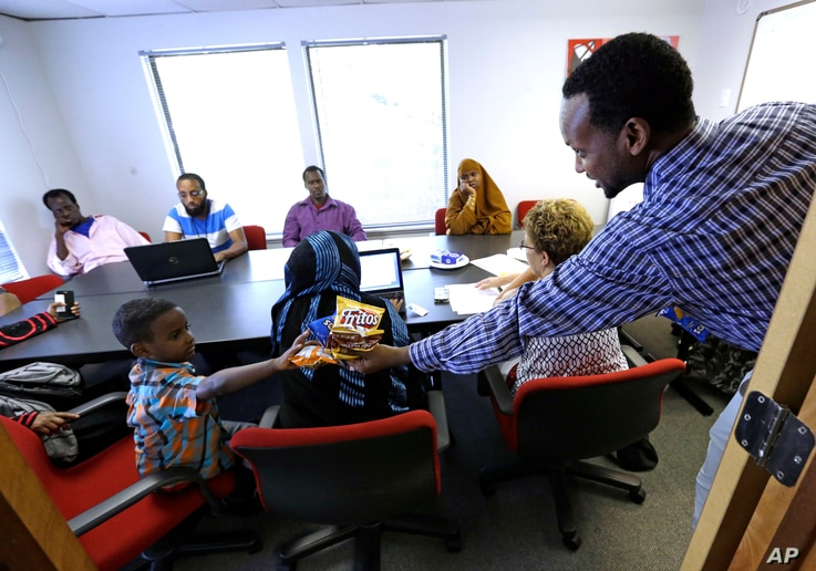 FILE - Somali immigrant leader Jamal Dar, right, who arrived in the U.S. two decades ago from Kenya, hands out snacks to a boy at a community engagement and civic language class for former Somali residents in East Portland, Oregon, July 21, 2015.