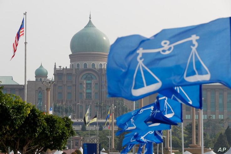 The flags of Malaysia's ruling party National Front coalition flutter in front of Prime Minister's office in Putrajaya, Malaysia, April 6, 2018. Malaysia's Prime Minister Najib Razak says he'll dissolve Parliament Saturday, paving the way for general...