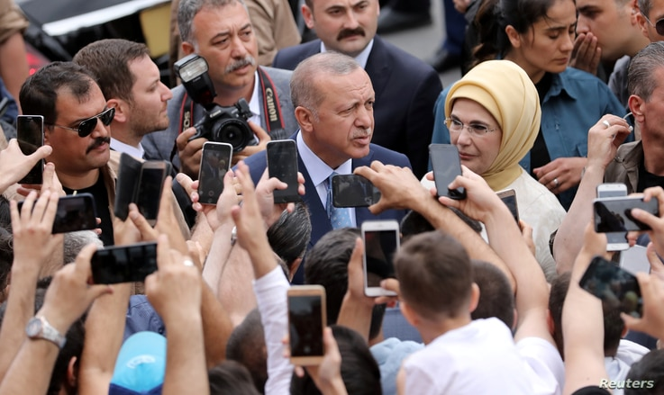 Turkish President Tayyip Erdogan poses for photographs as he leaves a polling station in Istanbul, Turkey, June 24, 2018.