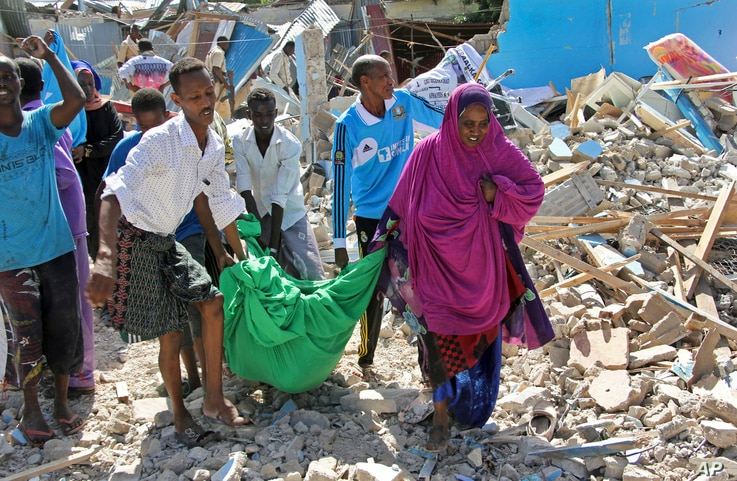 Somalis carry away the body of a civilian who was killed in a car bomb attack in Mogadishu, Somalia, June 20, 2017.