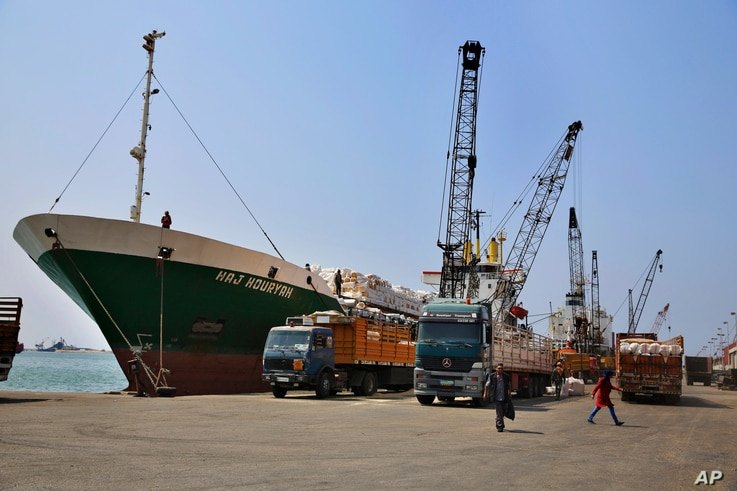 Cranes offload hay from a ship onto waiting trucks in the port of the northern city of Tripoli, Lebanon, Aug. 9, 2017.