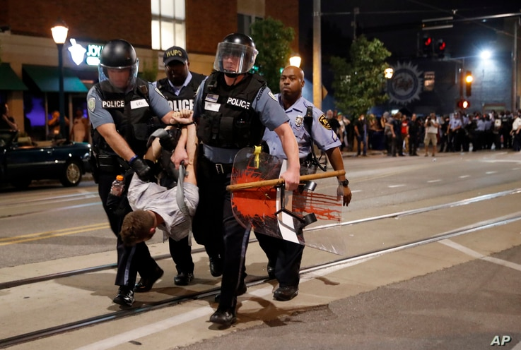 Police arrest a man as they try to clear a violent crowd, Sept. 16, 2017, in University City, Mo. Earlier, protesters marched peacefully in response to a not guilty verdict in the trial of former St. Louis police officer Jason Stockley.